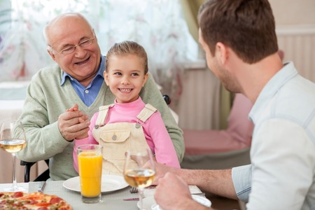 かわいい家族には、レストランのディナーがあります。話して、笑っています。老人が車椅子に座っていると彼の孫娘を採用 写真素材