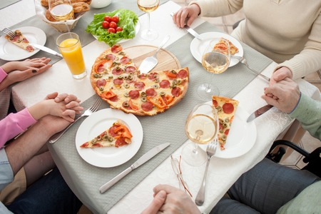 family praying: Cierre para arriba de los brazos de la familia ruegan junto antes de la cena. Est�n sentados en la mesa y de la mano Foto de archivo