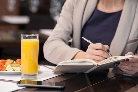 noting: Close up of hands of successful female business worker noting ideas in writing-pad. She is eating salad and drinking juice in restaurant Stock Photo