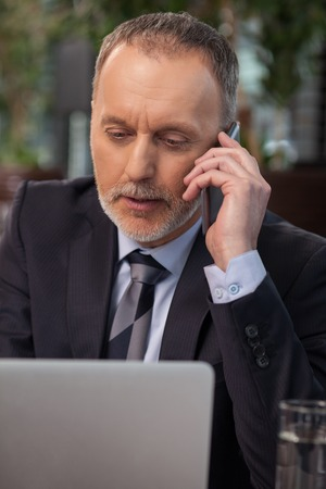 seriousness: Cheerful mature businessman is working in cafe. He is sitting at the table and talking on the phone. The man is looking at his laptop with seriousness