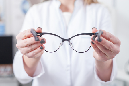 oculist: I have the eyeglasses for you. Close up of professional oculist holding glasses Stock Photo