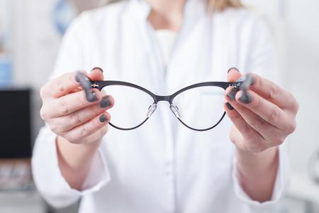 oculista: Tengo las gafas para usted. Primer plano de la celebración de las gafas profesional oculista