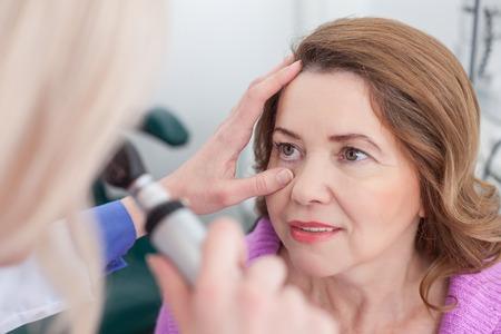 oculista: oculista hábil está examinando los ojos femeninos en la clínica. Ella es la celebración de una herramienta especial y dirigir láser en ojo femenino. La mujer está sentada y sonriente