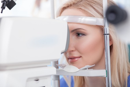research science: Beautiful young woman is having eye examination at the slit lamp in clinic. She is sitting and smiling