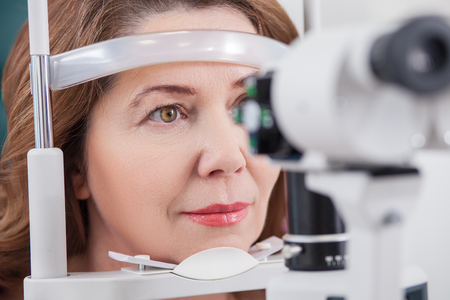 Pretty woman is looking into eye test machine with concentration in oculist lab. Focus on her face Stok Fotoğraf