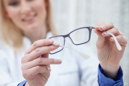 doctor giving glass: Try on these eyeglasses. Experienced optician is holding glasses and smiling
