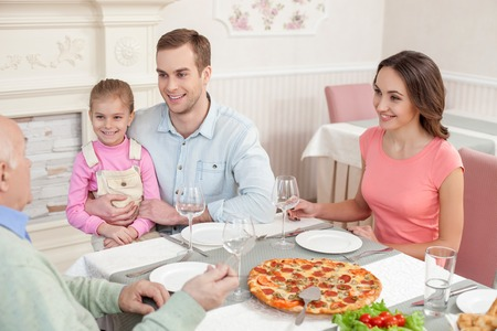 restaurant dining: Cheerful family is dining together at restaurant. They are sitting at the table and smiling. The married couple with their child are looking at old grandfather with joy Stock Photo