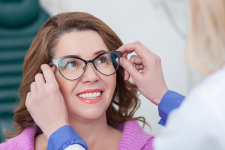 Wear this eyeglasses and you will see better. Experienced ophthalmologist is serving the patient. The woman is looking at the doctor with trust and smiling