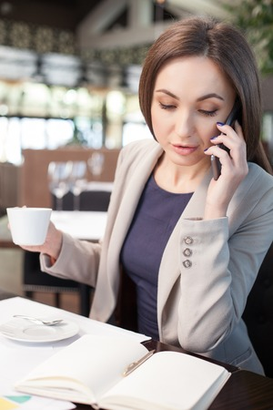 seriousness: Portrait of beautiful young businesswoman talking on the mobile phone in cafe. She is looking at her writing-pad with seriousness. The woman is drinking coffee Stock Photo