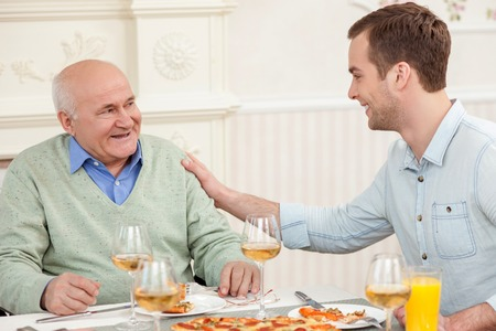 senescence: Cheerful old man is celebrating his birthday. His son is touching his shoulder with congratulations and smiling. They are sitting at the table and eating pizza