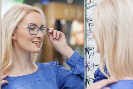 Beautiful blond girl is wearing eyeglasses in a store. She is looking at the mirror with satisfaction and smiling Stockfoto
