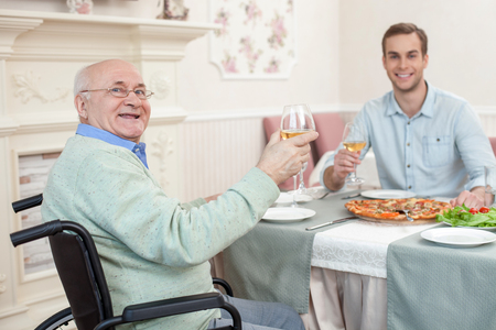 We like dining together. Cheerful mature father and his son are drinking wine in restaurant. They are looking at camera and smiling. The pensioner is sitting on wheelchair
