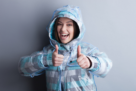 thumps up: This raincoat is wonderful. Attractive woman is standing and giving her thumps up. She is smiling. Isolated