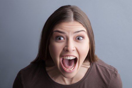 Portrait of woman screaming with horror. She is standing and looking at camera with panic. Isolated on grey background