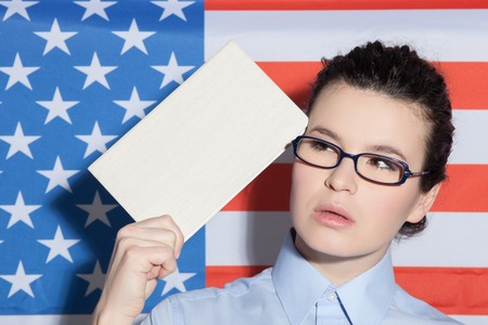 american sexy girl: Let me see. Waist up portrait of beautiful American businesswoman thinking about something seriously. She is standing in front of usa flag and holding a book near her head Stock Photo