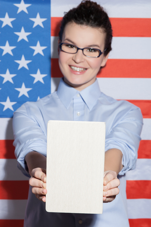 sexy pose: I like studying in United States of America. Cheerful woman is holding a book and showing it to the camera. She is standing near the usa flag and smiling. The lady is looking at camera happily