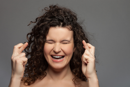 i hope: I am waiting for luck. Cheerful young woman is crossing her fingers with hope. She is standing with closed eyes and laughing. Isolated Stock Photo