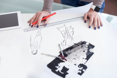 woman close up: Close up of arms of young designer drawing sketching with the help of a ruler and pencil. The woman is standing at the desk with a tablet on it