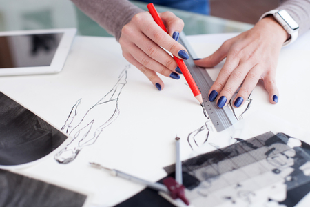 woman close up: Close up of hands of female photo artist drawing picture on the blueprint. The woman is standing and holding the ruler with pencil