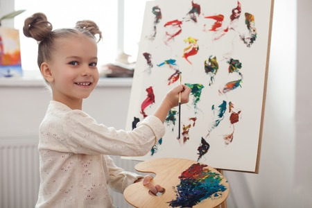 colegiala: Portrait of cute small girl learning to paint at home. She is standing near the canvas and holding the palette. The kid is looking at camera and smiling