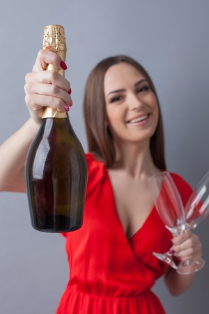 drink me: Drink this champagne with me. Portrait of pretty young woman showing a bottle to the camera. She is holding glasses and smiling. Focus on drink and isolated Stock Photo