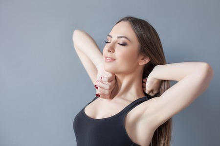 awaking: Cheerful fit girl is awaking herself. She is standing and stretching her arms. The lady is smiling with pleasure. Isolated and copy space in left side Stock Photo
