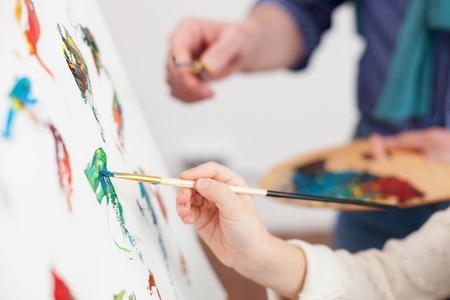 Close-up van de armen van grootvader en kleindochter schilderen samen Stockfoto