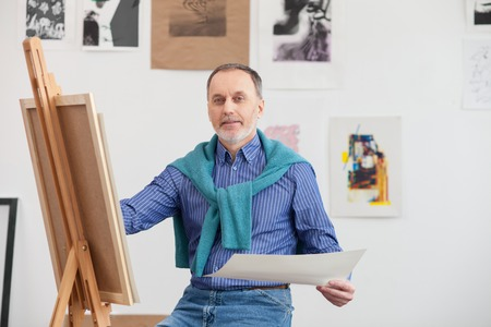 he old: Talented old painter is drawing a picture with aspiration. He is sitting near the canvas and holding a paper. The man is looking at camera and smiling Stock Photo