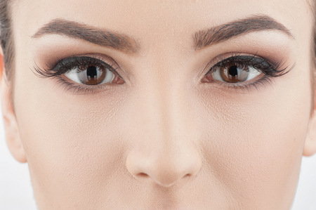 close up eyes: Close up of seductive female eyes. The young woman is looking at camera with passion Stock Photo