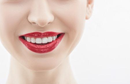 labios sensuales: Cerca de la cara de la mujer alegre sonriendo con felicidad. Sus labios seductores son rojos. espacio aislado y la copia en el lado derecho