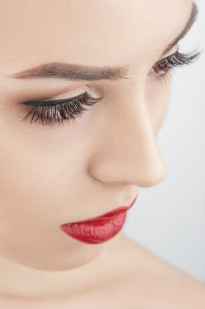 human lips: Close up of beautiful female face. The woman is looking sideways and flirting. Her red lips are expressing desire