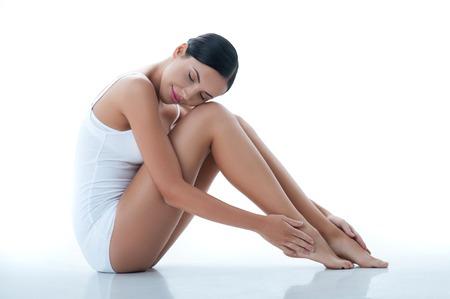 bragas: Hermosa mujer joven est� sentado y tocando sus piernas. Sus ojos se cierran con placer. Aislado Foto de archivo