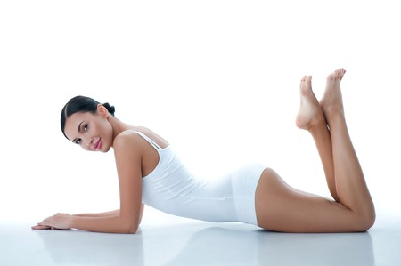 Beautiful young woman is lying and relaxing at spa. She is looking at camera and smiling flirtingly. Isolated Stockfoto