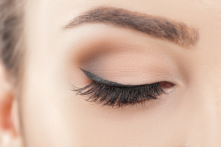 Close up of female closed eye with eyeshadow and cosmetics on it