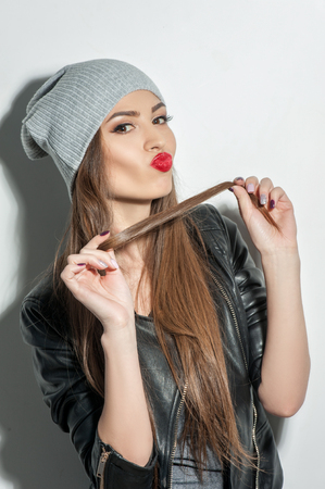 human lips: Waist up portrait of female rocker sending kiss to the camera. She is standing and posing. The woman is playing with her hair and looking forward with desire. Isolated Stock Photo