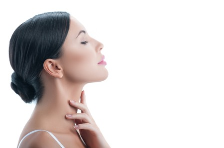 female body: Waist up portrait of beautiful girl applying cream on her neck. She is standing in profile. The girl is raising her chin with confidence. Isolated and copy space in right side Stock Photo