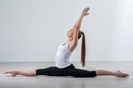 Skillful female athlete is doing the splits. She is raising her arms up and clasping them together Stock Photo