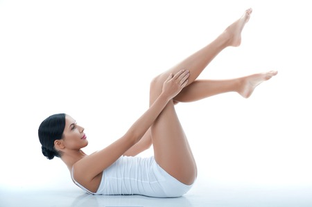 smooth: Portrait of attractive young woman lying and raising her legs up. She is touching her smooth feet with enjoyment. Isolated