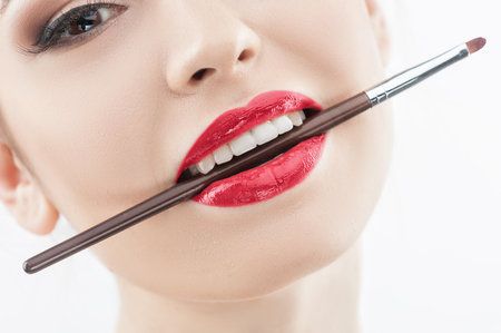 human lips: Attractive young woman is holding lipstick brush in her mouth. She is looking at camera with passion. Isolated Stock Photo