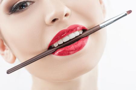 labios sensuales: La mujer joven atractiva es la celebraci�n de cepillo de l�piz de labios en su boca. Ella est� mirando la c�mara con pasi�n. Aislado