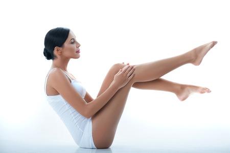jungen unterwäsche: Portrait der recht dünnen Mädchen Eincremen auf ihre Beine. Sie sitzt und hob die Füße. Die Dame lächelt. Isoliert