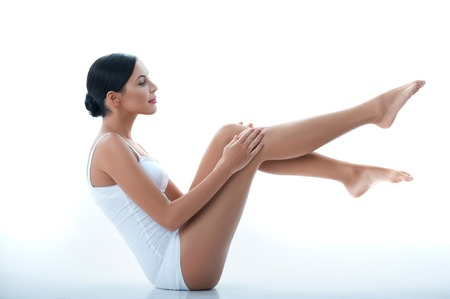 Portrait of pretty slim girl applying lotion on her legs. She is sitting and raising her feet. The lady is smiling. Isolated