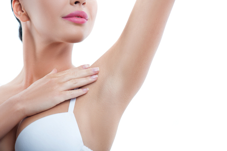 woman close up: Cheerful girl is touching her smooth armpit with satisfaction. She is standing and raising her arm up. Isolated and copy space in right side