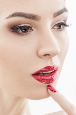finger on lips: Close up of female face with beautiful make-up. The young woman is touching her finger to her chin with desire. Her manicure and lips are red