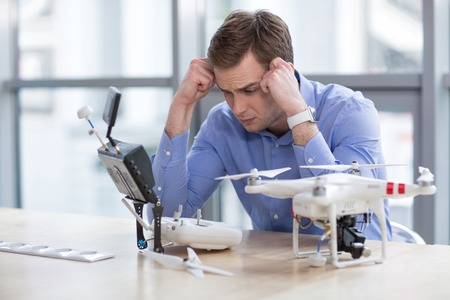 projecting: Portrait of skillful quadrocopter maker projecting a drone with frustration. He is sitting at the desk in his office. The man is looking at the remote controller pensively