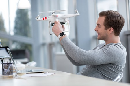 projecting: Professional young quadrocopter maker is projecting a new device. He is holding a quadrocopter and smiling. The man is sitting at the desk in his office