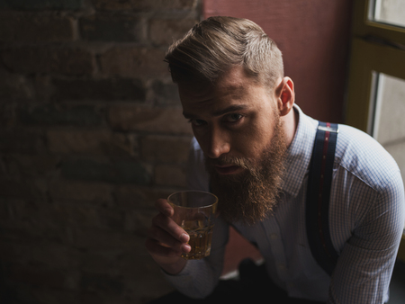 Portrait of cheerful bearded man drinking expensive whisky. He is sitting on the windowsill and looking at camera with seriousness Reklamní fotografie - 53386458