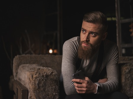 i hope: I am waiting for your call. Handsome bearded guy is expressing his sadness. He is sitting in the armchair at home. The hipster is holding a mobile phone and looking aside with hope