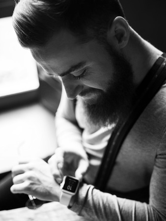 blackandwhite: Black-and-white portrait of cheerful bearded man from retro time. He is looking at the smart watch on his arm and smiling. The man is sitting and holding eyeglasses