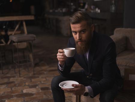 오래 된 식당에서 차 한 잔 마시는 쾌활 한 젊은 남자의 초상화. 그는 앉아서 자신감을 갖고 카메라를보고 있습니다. 그 남자는 큰 수염을 가지고있다.  스톡 콘텐츠